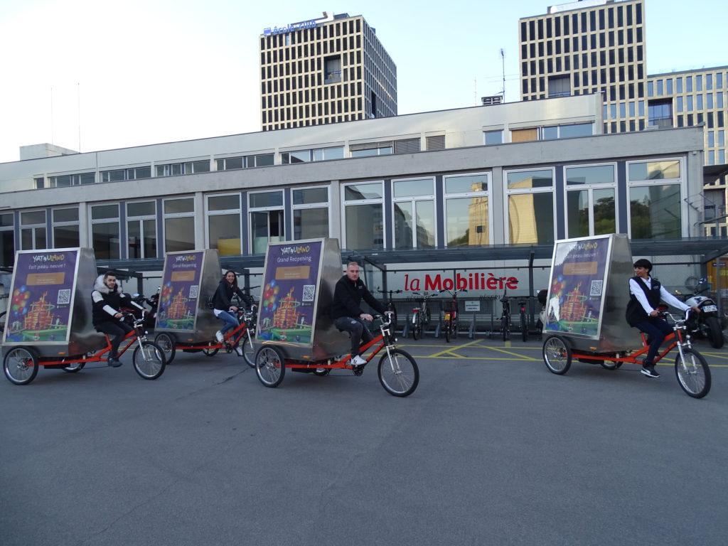 quatre vélos électriques publicitaires à Genève et quatre promoteurs habillés aux couleurs de Yatouland