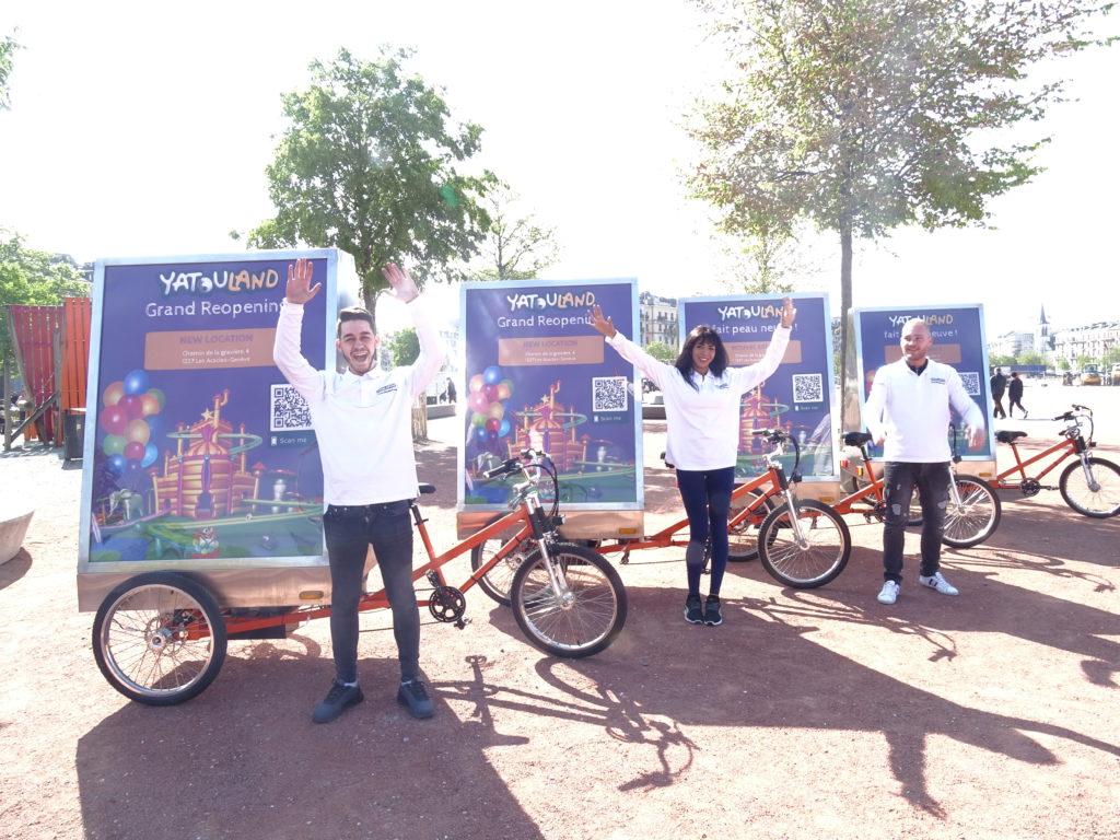 quatre vélos électriques publicitaires à Genève et trois promoteurs habillés aux couleurs de Yatouland