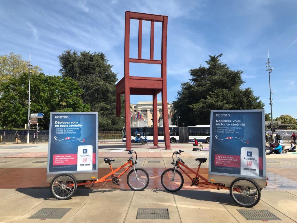 deux vélos électriques publicitaires affichant une campagne publicitaire pour la société de VTC Kapten parqués sur la place des Nations à Genève