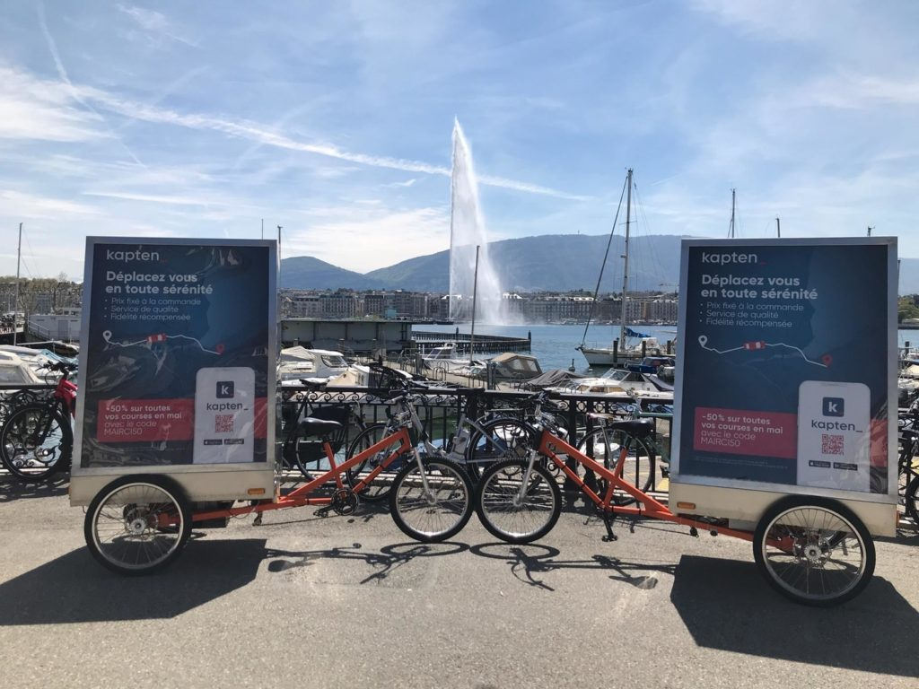 vélo électrique publicitaire de street marketing au bord du lac de genève. on aperçoit le jet d'eau