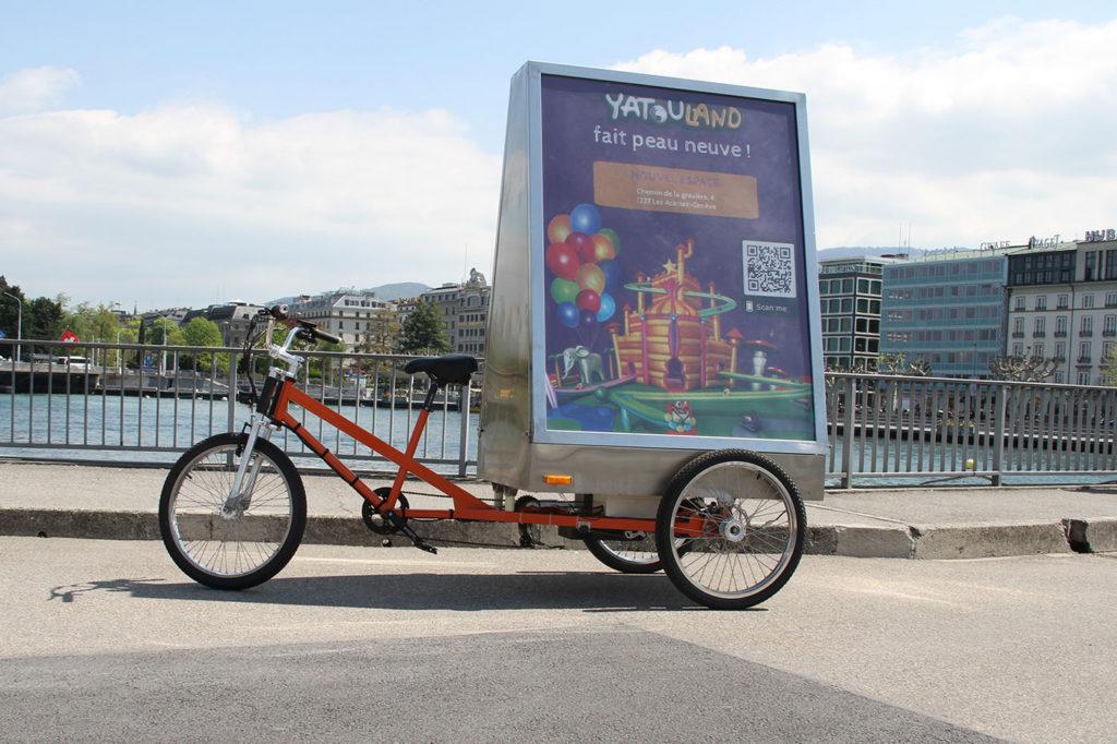 Vélo électrique publicitaire à Genève affiche de la campagne MediaShift pour Yatouland