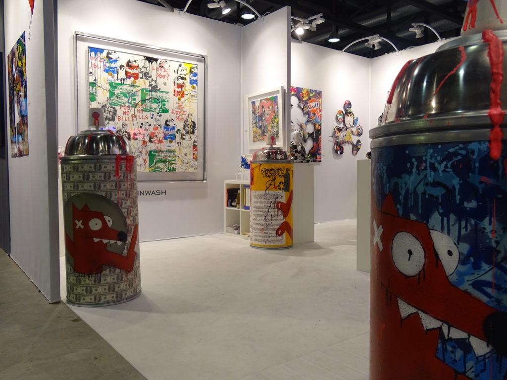 Aperçu du stand de la galerie BELAIR FINEARTau sein du Lausanne ArtFair. On aperçoit des bombes de peintures  géantes, l'outil de base du Street-art réalisées par PIMAX et divers tableaux aux couleurs très vives.