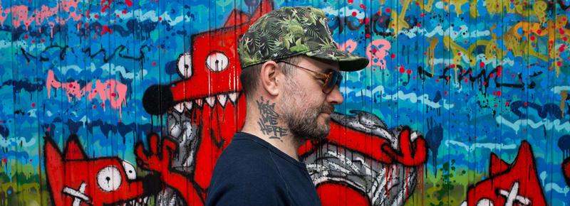 Vue de profil de PIMAX artiste Street-art . En arrière plan une fresque représentant Nourf, son alter ego artistique.