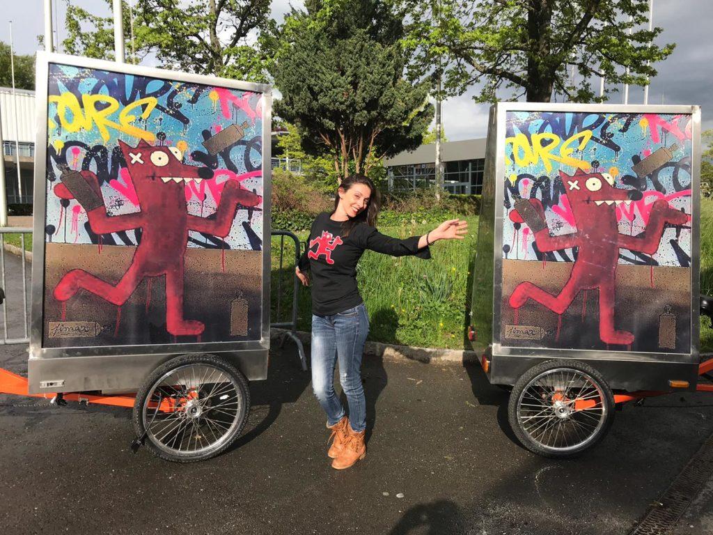 Promotrice entouré de 2 vélos publicitaires par une fin d'après-midi ensoleillée. BELAIR FINEART a contacté MediaShift pour un partenariat autour de Pimax artiste de Street-art