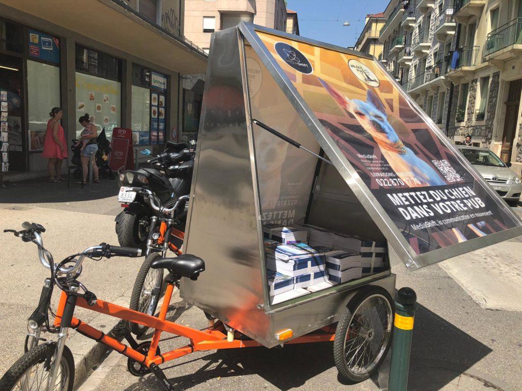 MediaShift, vélo électrique de livraison et publicitaire avec les portes latérales ouvertes, garé en ville à Genève. le livreur est en tournée