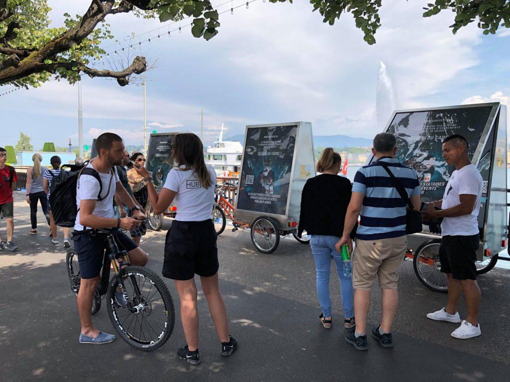 les 4 vélos sont garés sur le quai du Mont-Blanc, les promoteurs vont au devant du public pour leur parler de HubEvent l'agence de création événementielle
