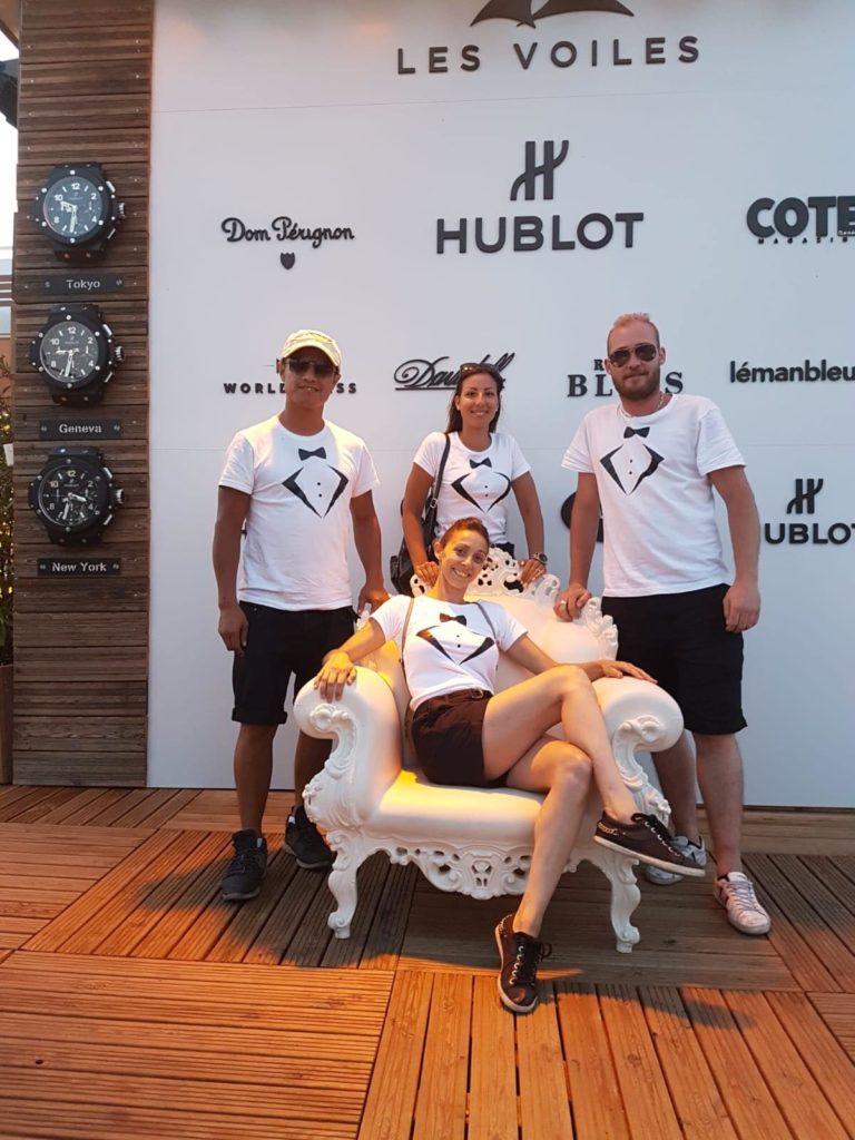 Quatre promoteurs de chez HubEvent , deux garçons, deux filles entourant une demoiselle assise dans un fauteuil baroque. tous sont habillés d'un t-shirt reprenant les codes du smoking pour un événement réussi