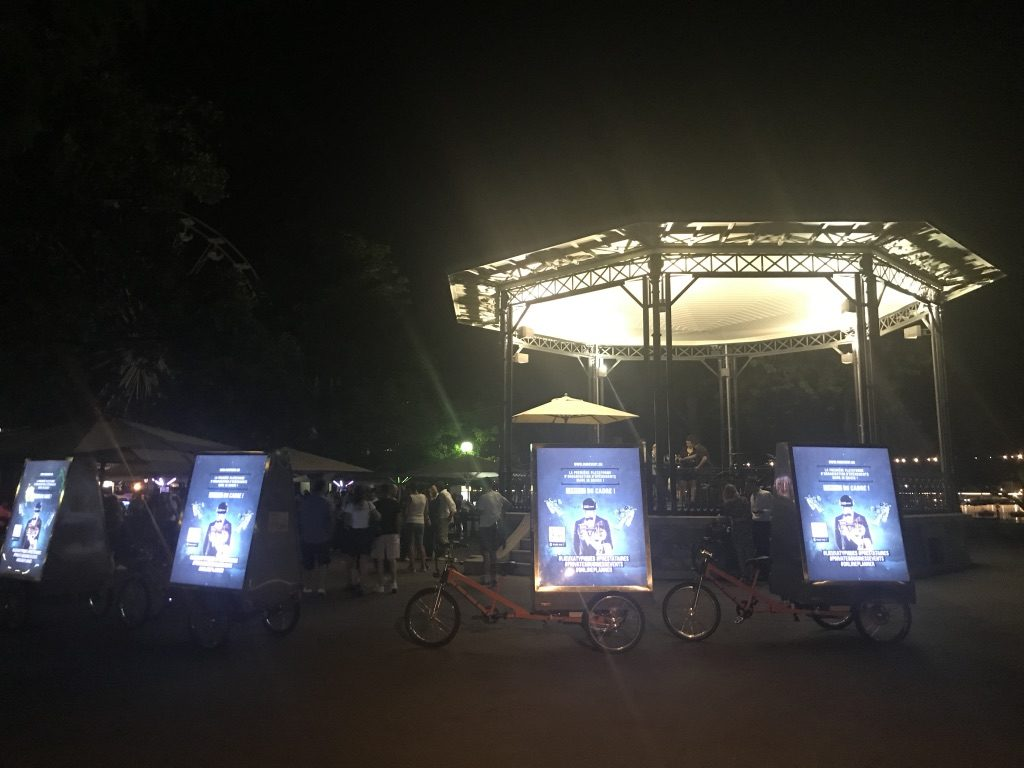 les quatre vélos électriques en session nocturne ( rétro-éclairés ) parqués devant le kiosk du jardin anglais à Genève lors de la campagne pour HubEvent