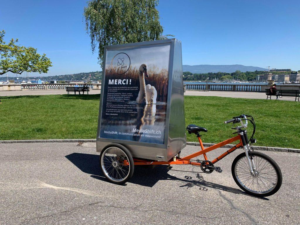 On peut voir un vélo publicitaire électrique stationné sur la rive du lac, portant une affiche avec un signe dans l'eau afin de remercier toutes les professions qui étaient en première ligne pendant la pandémie du COVID-19